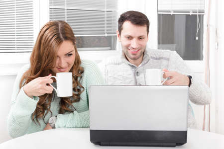 Close up beautiful couple working and looking on laptop at home with a cup in hands drinking tea or coffee photo