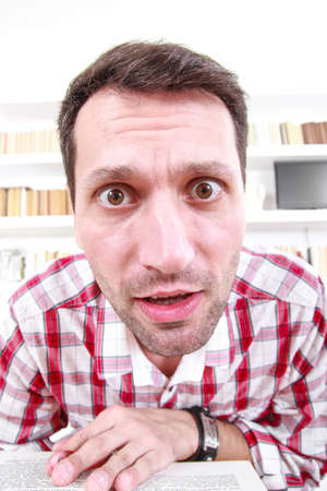 close up of nutty confused and shocked professor or student with book in his hands, living room atmosphere with library background Stock Photo