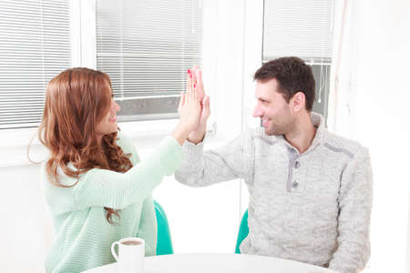 agrees: happy couple agrees with the agreement. Having agreement with gesture give me five, symbol hand on hand. Causal couple clapping hands in their living room.