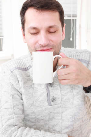 Portrait of a calm man having a coffee in his living room. Good looking adult man savouring the aroma of a cup of fresh hot coffee or tea during a business break smiling with his eyes closed in enjoyment.