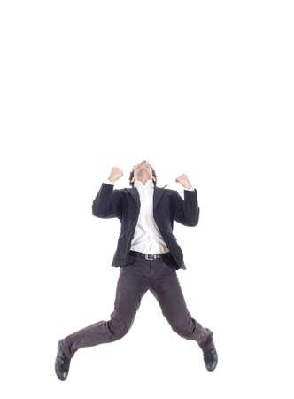 legs spread: Uomo d'affari che salta di gioia e di successo con le gambe divaricate, isolato su uno sfondo bianco