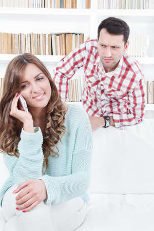 jealous worried man peering over the shoulder of his girlfriend while she is talking on the phone smiling
