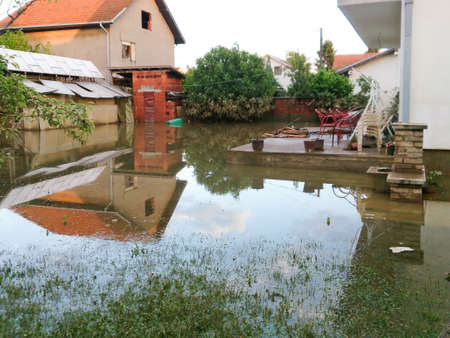 condition of house with a yard after floods, flood and disaster in town Obrenovac in Serbia, damaged houses and property, state or condition after terrible flood, destroyed and abandoned city photo