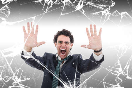 angry and shocked businessman holding broken glass wall, looking to camera, isolated on white background, Place for text photo