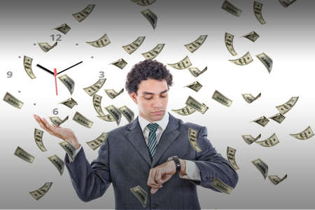 Businessman looking at his watch with money rain around him, rich man in suit measuring time on clock surrounded by flying dollars Stock Photo