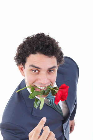 the seducer: confident man seducer in a suit holding a red rose in his mouth with a seductive view or look while pointing his hand or finger and called to come