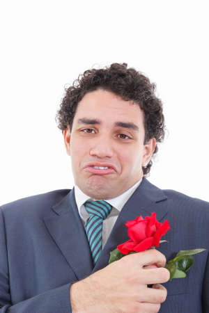 adult sad and very disappointed man in suit with weird geeky face expression  holding with his hand rose flower which is in his jacket pocket photo