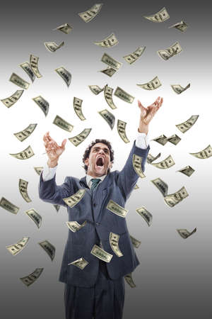 excited man catching money falling around him, businessman under money rain, yelling man reaching for flying banknotes Stock Photo