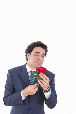 the seducer: handsome man seducer in a business suit with weird geeky face expression holding rose in his hand and smelling it, isolated on white background
