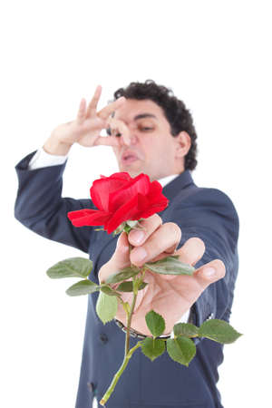 hand holding flower: man in suit throws a rose and gives it to the camera while the other hand holds a stuffy nose with his hand because of the smell of flowers, isolated on white background