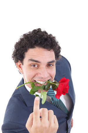 the seducer: man seducer in a suit holding a red rose in his mouth with a seductive view or look while pointing his hand or finger and called to come Stock Photo