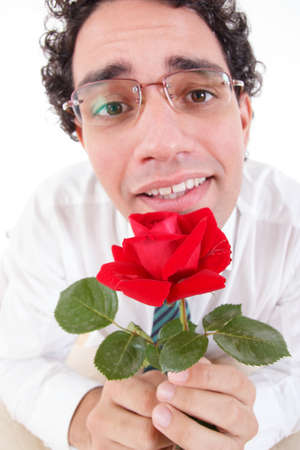 Romantic silly man in love holding red rose, Guy with puppy look offering a rose wearing glasses, Flirty cute guy with flower Stock Photo
