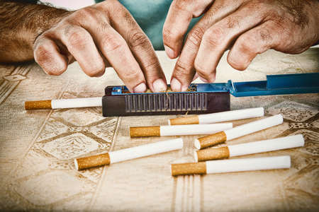 Male hands making cigars with rollings filled with tobacco to satisfy his habit and to smoke handmade cigarettes