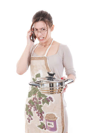 pissed: Nervous housewife dressed in apron holding pot and talking on mobile arguing pissed off