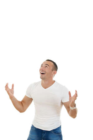 smiling man in t-shirt and jeans looking up in blank copy space with a slightly raised his hands as if collecting or catches money from above