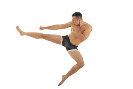 Excellent fight pose of intense man boxer with a kick in the air isolated over white background, Jiu jitsu or kick box or thai boxing