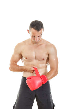 Fit muscular man putting his boxing gloves in front of camera, preparing for training over white background photo