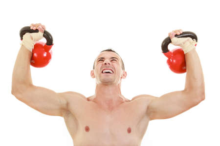 strong athletic half naked man holding and lifting red kettlebells weights  in front of camera photo