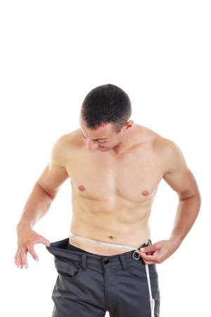 seminude: semi-nude semi-bodybuilder with measuring tape around his waist with evidence of weight loss by looking at hole in his pants Stock Photo