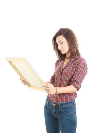 intrigued: intrigued casual pretty woman holding and looking at art painting in studio