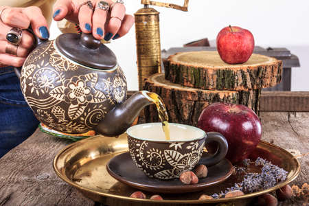 Woman pouring tea from teapot on vintage wooden table with hazelnuts apples and golden coffee mill in traditional style