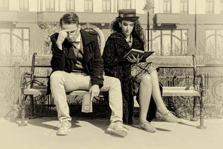 impatience: Young fashionable couple in quarrel sitting on bench in old town reading book in vintage style