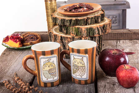 two empty cups for tea on retro wooden table next to the bark of a tree with an red apples next to photo