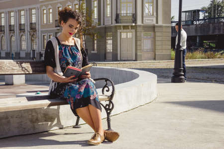 girl reading book on bench in town while  man is stocking  in the background behind her behind pole photo