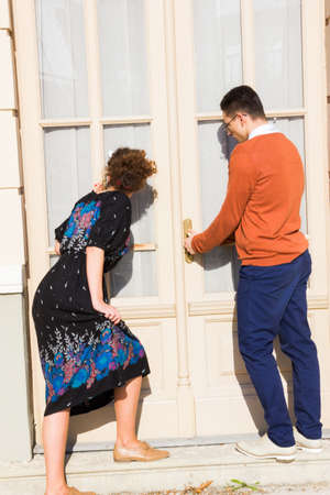 trying: man with glasses in the orange sweater with woman  trying to open the door while looking through the window and curtain , couple buys a house