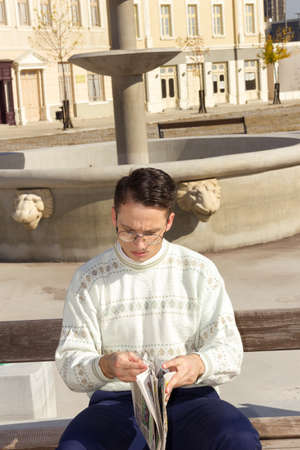 man with glasses in white sweater reading newspaper on bench next to fountain in town photo