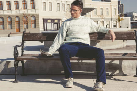 vintage photo of man with glasses in white sweater reading newspaper on bench next to fountain in town photo