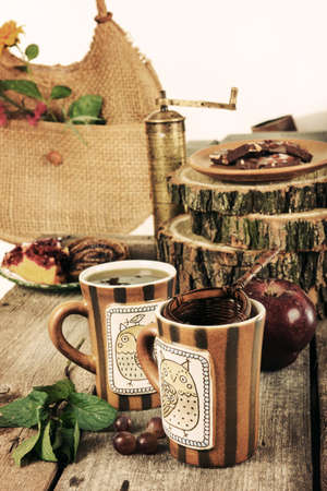 Two mugs filled with hot tea on old wooden table surrounded by homemade cookies chocolate and apples photo