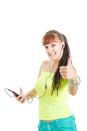 Young modern woman showing thumb up listening to music over headphones attached to smart phone Stock Photo