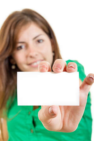 pretty smiling young woman or girl in green shirt holding in hand bussiness card against white background. Copy space for text and marketing ideas and slogans. Focus on blank white card photo