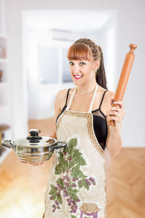 sexy housewife: Beautiful young woman in the kitchen wearing apron holding pot and rolling pin smiling , Cooking concept , Sexy housewife in the kitchen Stock Photo