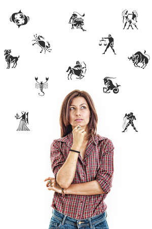 Ordinary casual beautiful woman surrounded with zodiac signs thoughtfully looking up with questionable face expression in jeans and shirt, photo conception problems with horoscope, good and bad sides and features