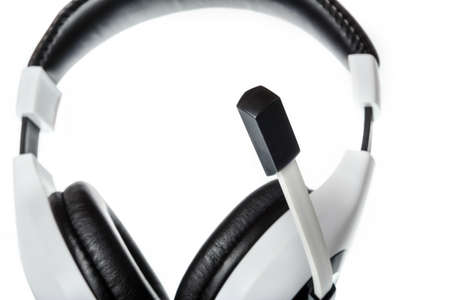skype: Black and white pc or computer headphones with focus on microphone side view isolated on white. Voip and agency or company internet calls photo compsition