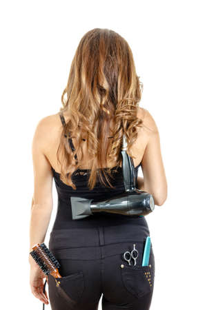 Professional caucasian brunette female hairdresser posing from behind with hairdryer on her back with brush and comb in back pocket, isolated on white backgropund. She has beautiful, long and healthy brown hair photo