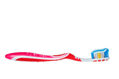 Red toothbrush with blue two color toothpaste on light surface. Photo of dental hygiene and health maintenance. Object isolated on white background without shadows photo