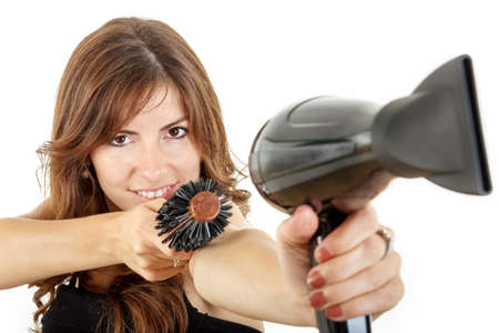 Beautifule female hairdresser using hairdryer and hairbrush pointing at camera smiling photo