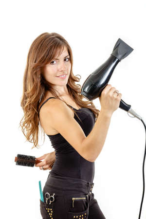Smiling professional caucasian brunette female hairdresser holding hairdryer in hand with comb in back pocket, isolated on white backgropund. She has beautiful, long and healthy brown hair