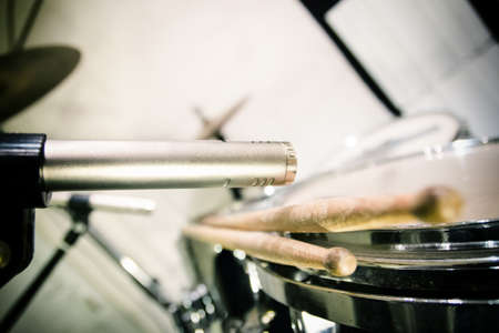 atmospheric: vintage retro professional microphone placed close to drums with sticks, preparation before recording in music studio