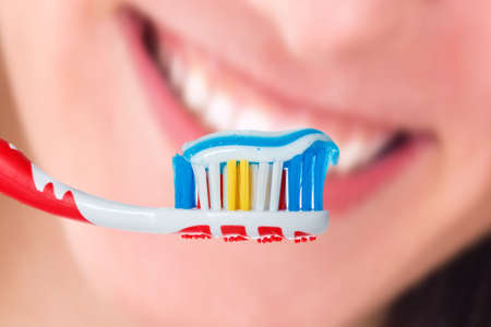 Red toothbrush with blue two color toothpaste with human smile background. Photo of dental hygiene and health maintenance photo