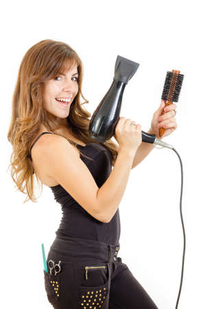 Smiling and happy professional caucasian brunette female hairdresser holding hairdryer in left hand and brush in right hand with comb in back pocket, isolated on white backgropund. She has beautiful, long and healthy brown hair photo
