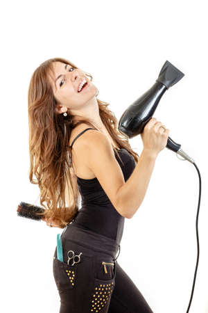 hairdryer: Smiling and happy professional caucasian brunette female hairdresser holding hairdryer in left hand and brush in right hand with comb in back pocket, isolated on white backgropund. She has beautiful, long and healthy brown hair