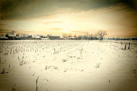 winter's tale: Winters Tale. Winter landscape with snowy countryside village next to cornfield covered in white snow cover at sunset or sunrise. Rural home in winter time. Vintage photo Stock Photo