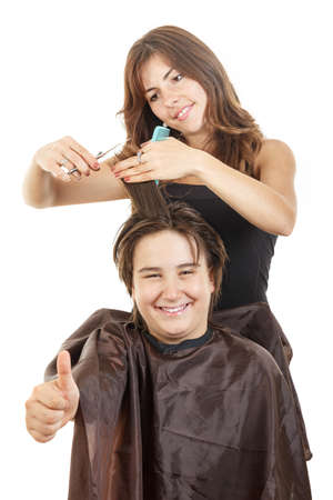 cute young male chubby child kid or boy smiling with long hair with thumb up at happy female hairdresser cutting his hair while he sitting in chair with bosco