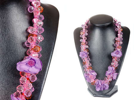 showpiece: Beautiful stylish handmade handcrafted woman bijouterie or female vintage fashion antique pink colorful jewelry necklace on black model showpiece doll isolated on white background. Close up shoot Stock Photo