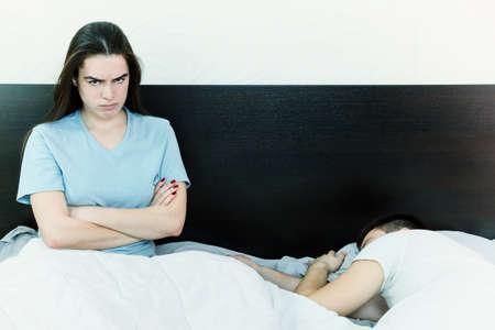 sexo pareja joven: Insatisfecho joven y bella mujer en la cama con expresi�n triste y decepcionado en su cara, problemas sexuales en la larga relaci�n matrimonial mientras que el hombre durmiendo. La saciedad entre cauc�sico, desinter�s