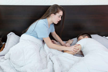 Woman  wakes up man who is late for work, delays due to fatigue. Wear of marriage. Couple was asleep in bed. Impatience woman wakes up tired husband.